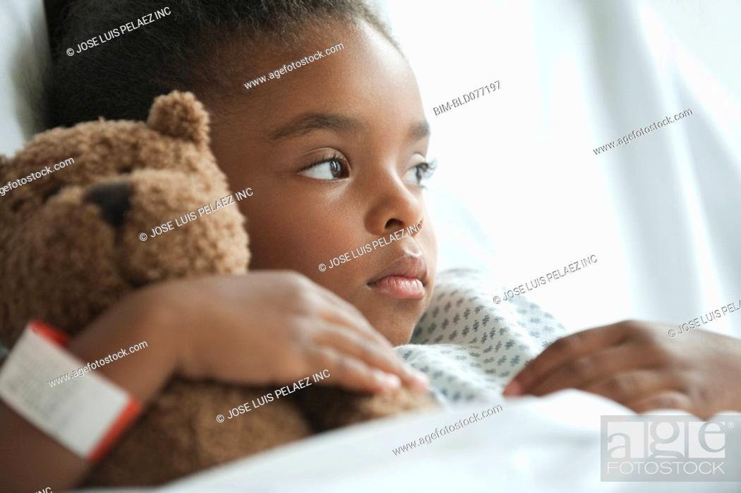 Stock Photo: Mixed race girl in hospital bed with teddy bear.