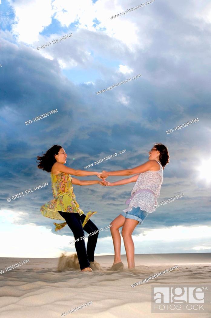 Stock Photo: Girlfriends twirl in sand.