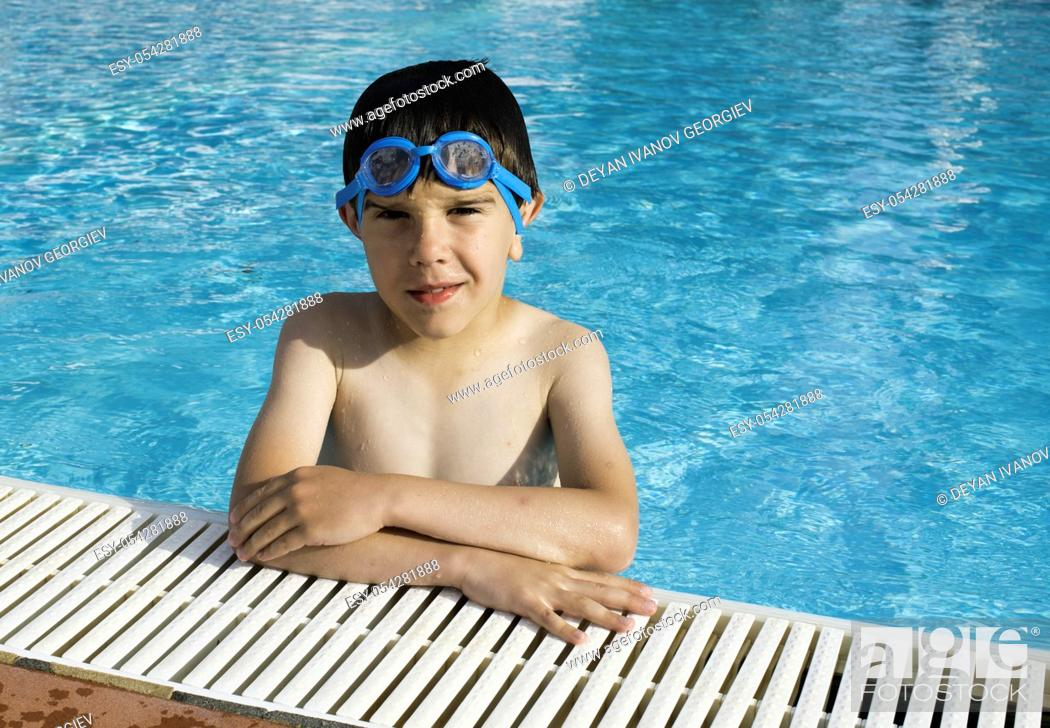 Stock Photo: Child in swiming pool. Blue glasses.
