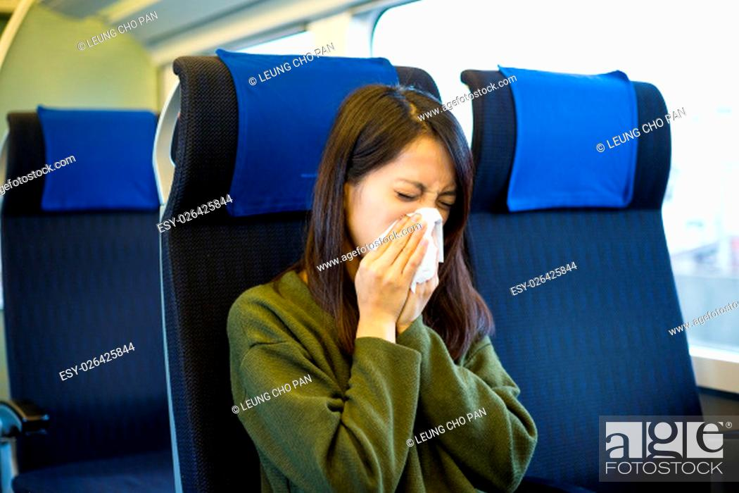 Stock Photo: Woman sneezing inside train compartment.