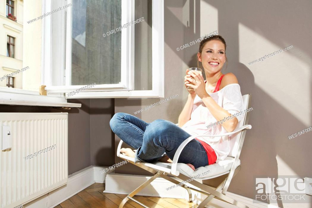 Stock Photo: Germany, Berlin, Young woman sitting at open window, smiling.