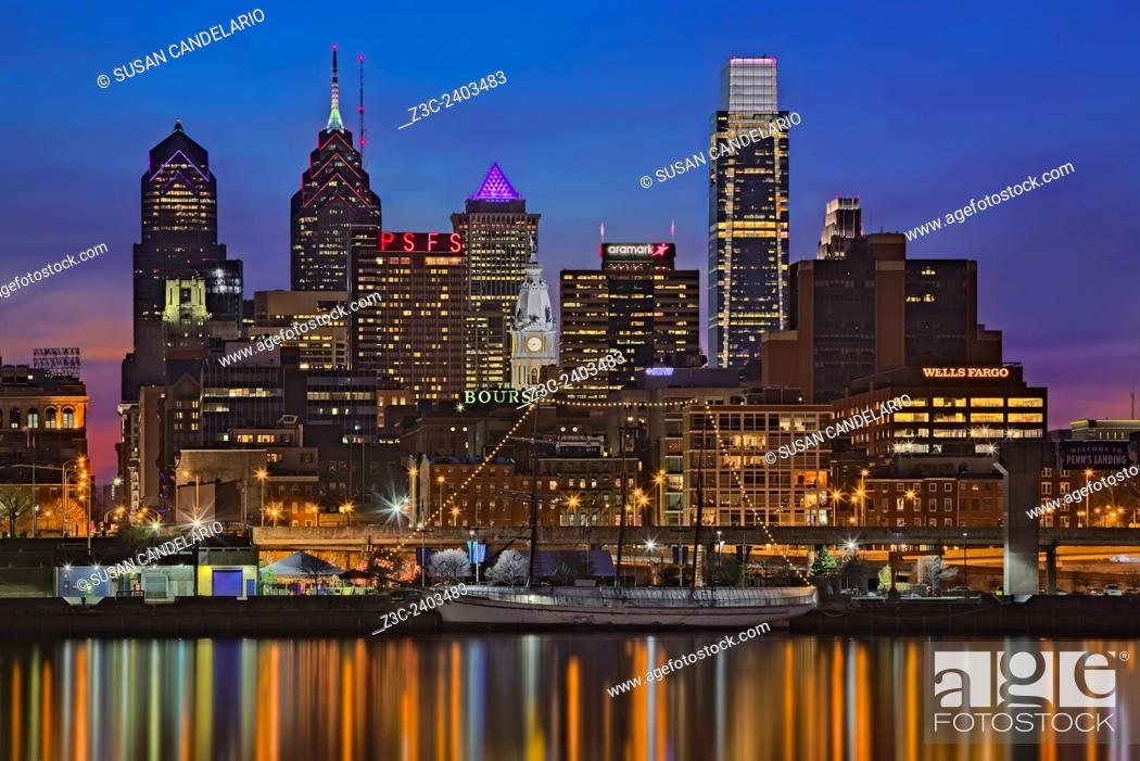 Stock Photo: Welcome To Penn's Landing - A view to the Philadelphia Skyline during the blue hour at twilight. The illuminated urban skyline shows the Comcast Building.