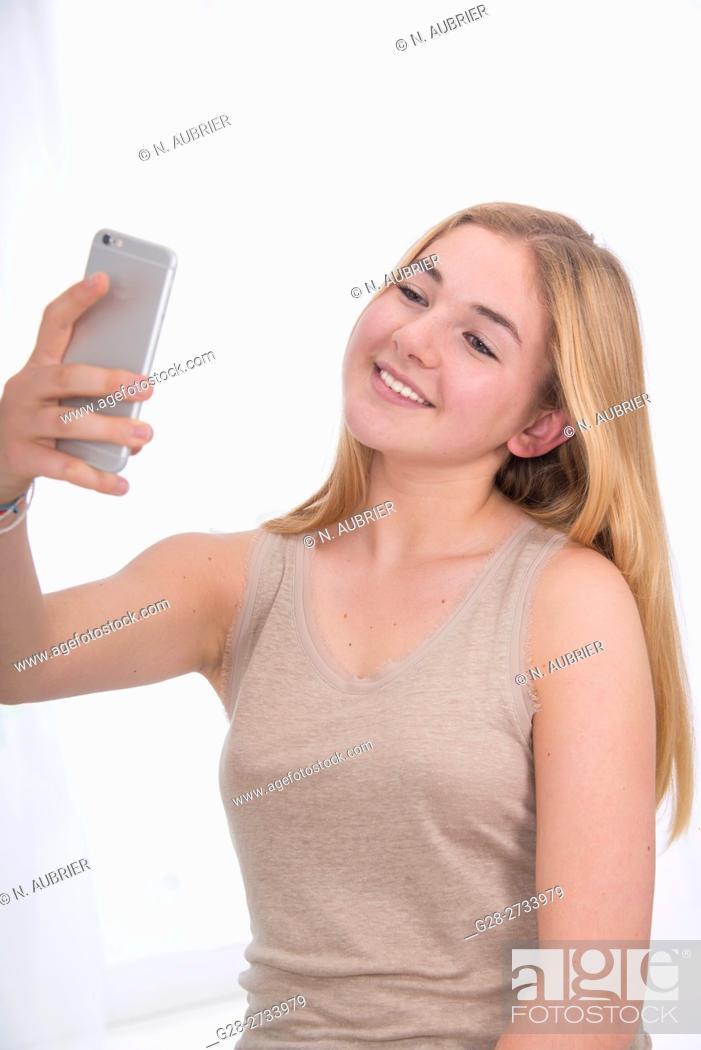 Stock Photo: Happy young blond teenage girl making a selfie with her i phone.