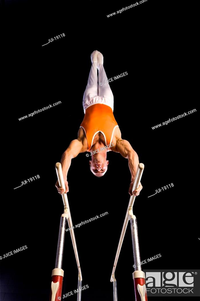 Stock Photo: Male gymnast performing on parallel bars, low angle view.