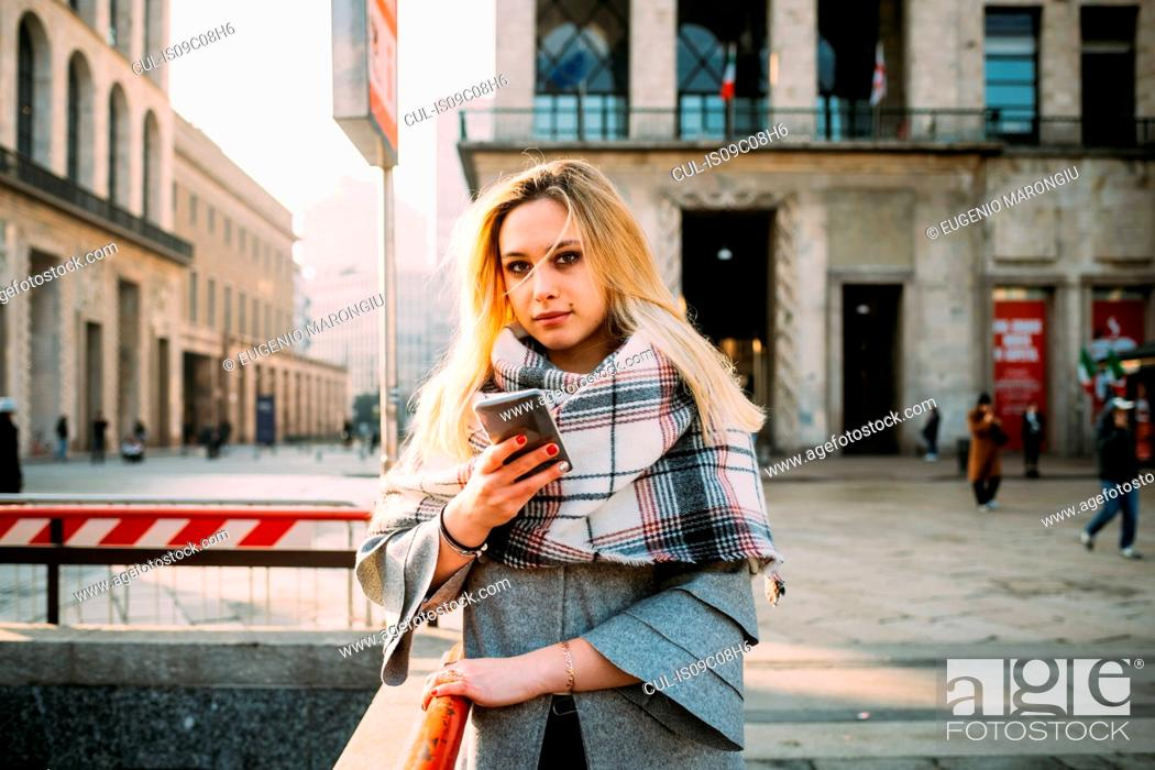 Stock Photo: Young woman with smartphone by underground station, portrait, Milan, Italy.