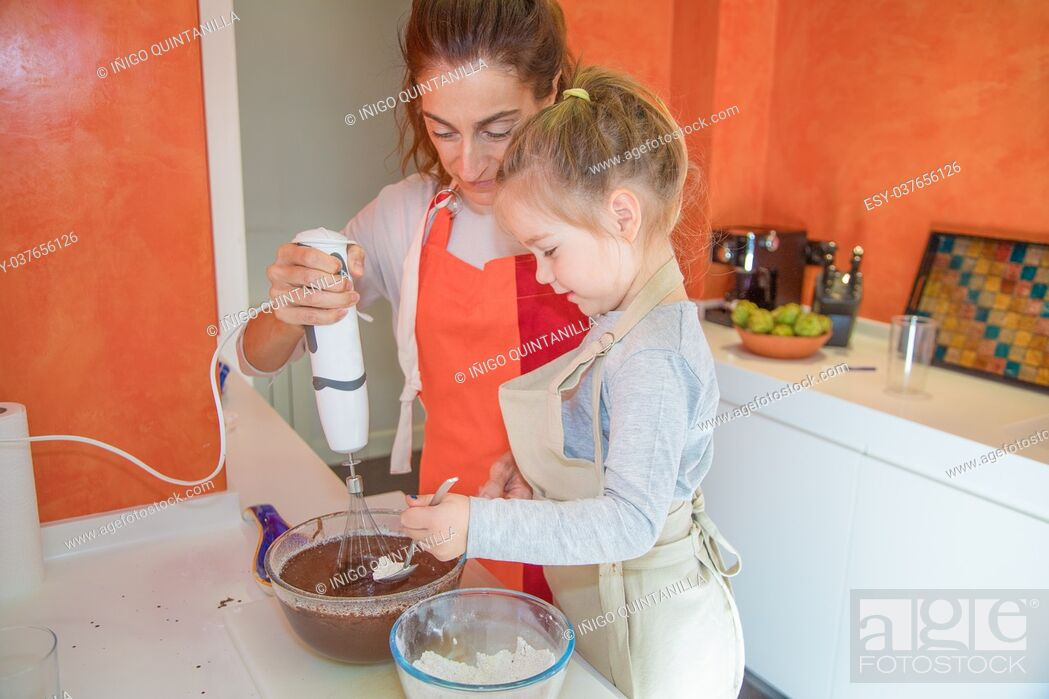 Imagen: four years old girl pouring flour on chocolate cream and woman whisking with electric mixer in glass bowl, in teamwork, cooking a sponge cake at kitchen home.