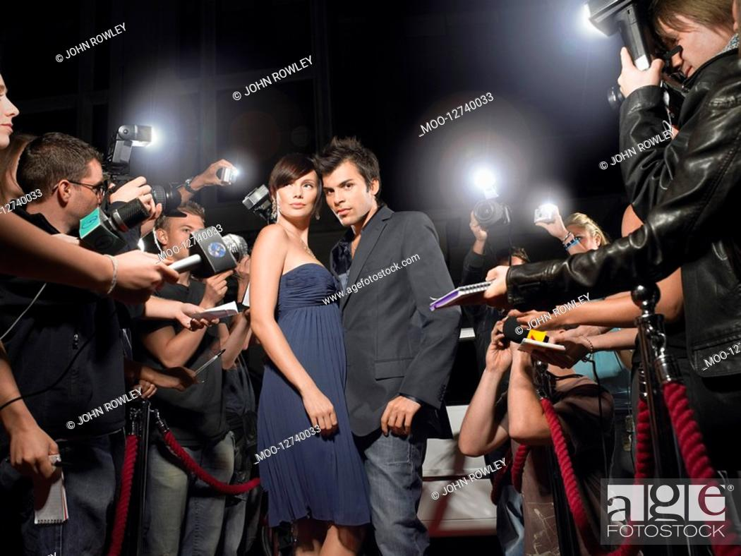 Stock Photo: Couple posing on red carpet being photographed by paparazzi.