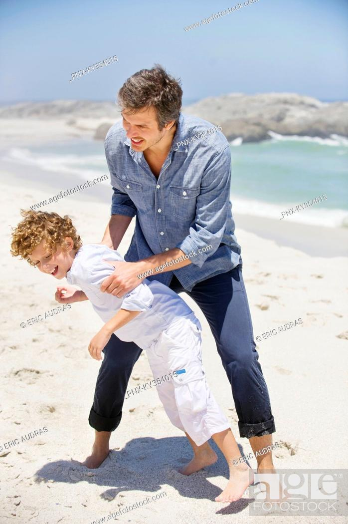 Stock Photo: Man playing with his son on the beach.