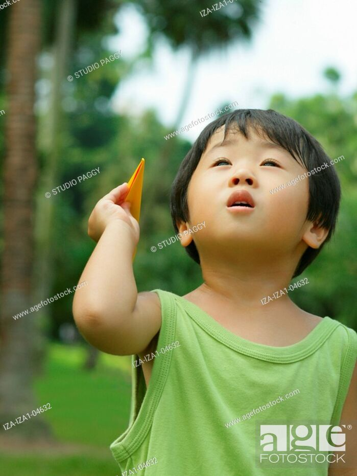 Imagen: Close-up of a boy holding a paper airplane.