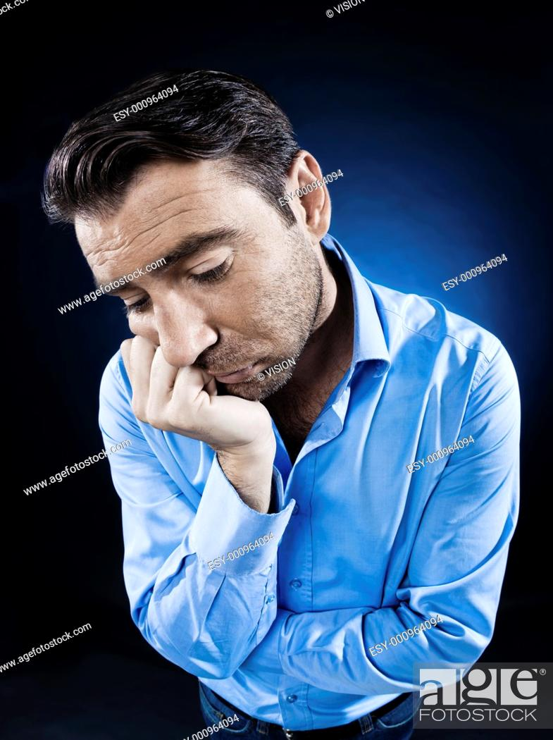 Stock Photo: caucasian man unshaven portrait sulk tired isolated studio on black background.