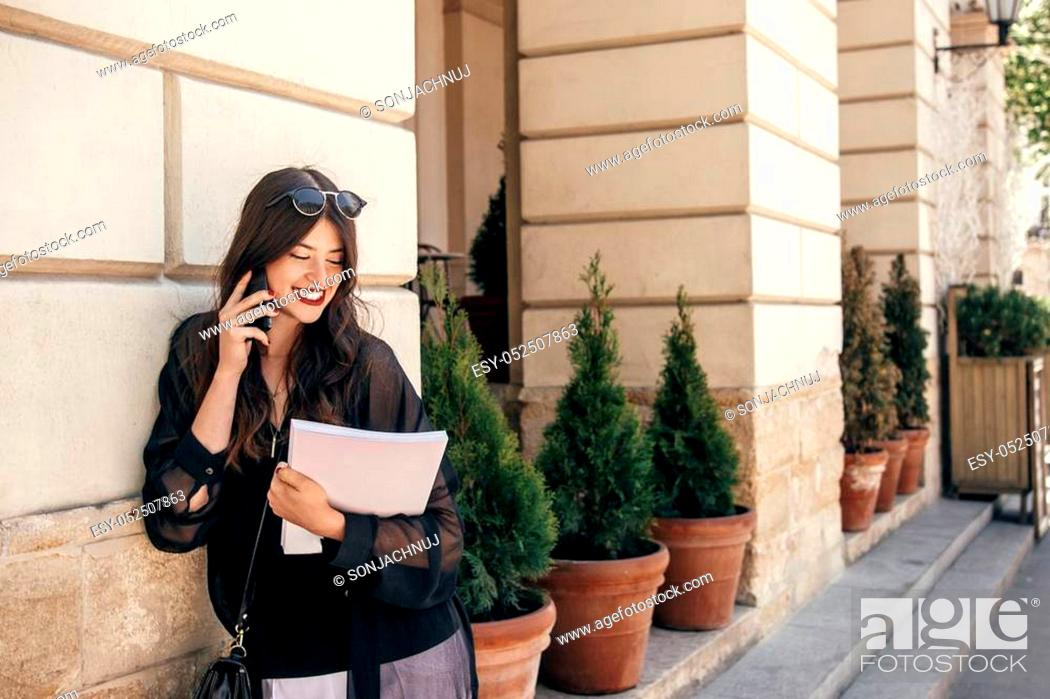 Stock Photo: beautiful stylish woman walking in sunny city street, holding phone and magazine. happy hipster girl dressed in fashionable outfit.