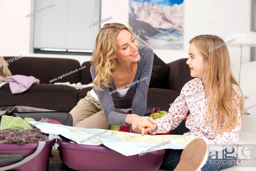 Stock Photo: Germany, Leipzig, Mother and daughter looking at map, smiling.