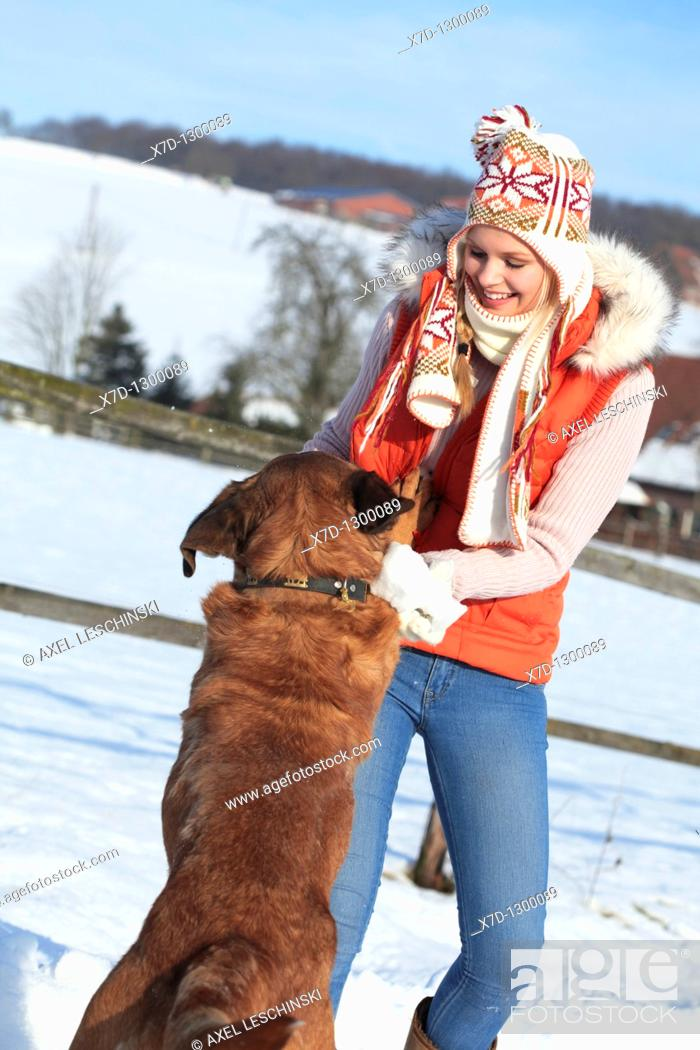 Stock Photo: woman playing in winterly landscape with dog.