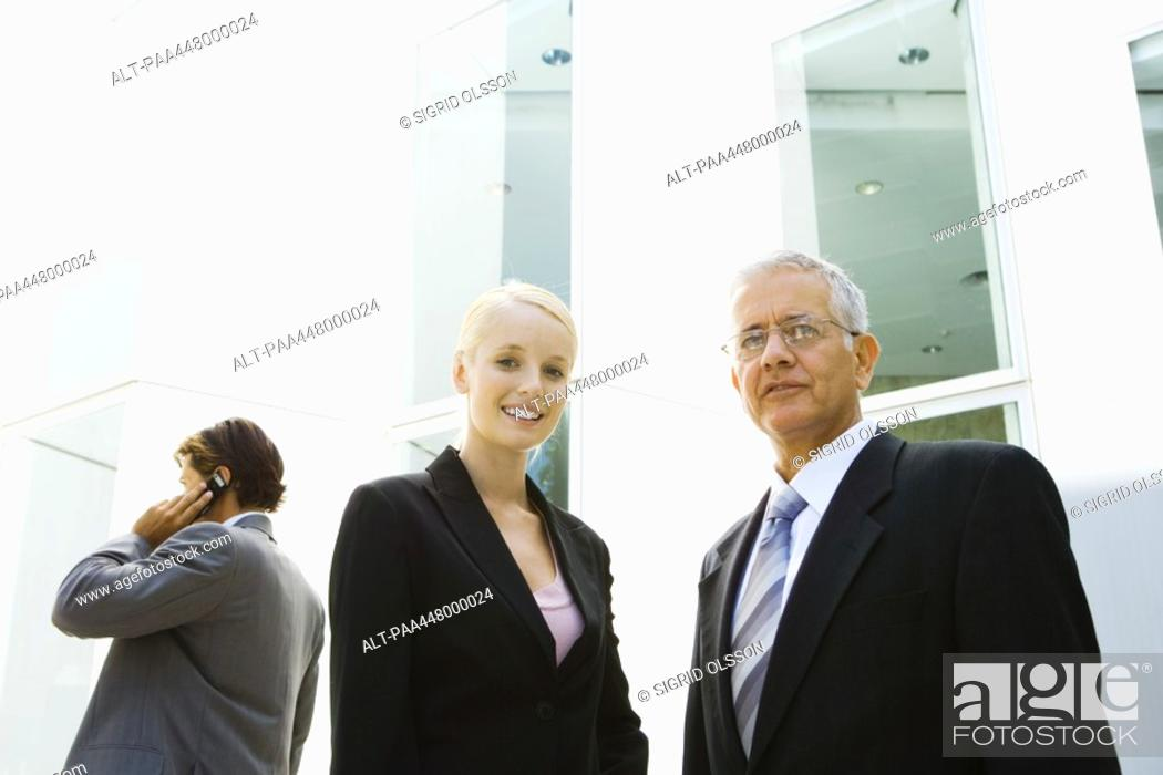 Stock Photo: Mature businessman and young businesswoman, low angle view.