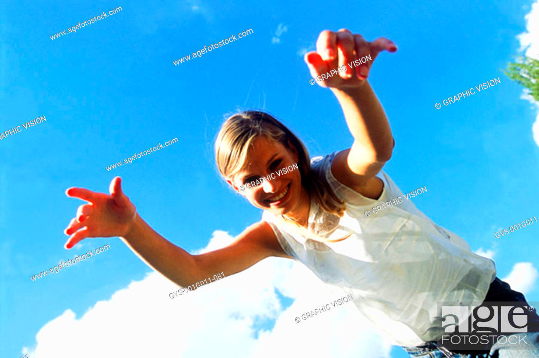 Stock Photo: Low angle view of a young woman with arms reaching forward.