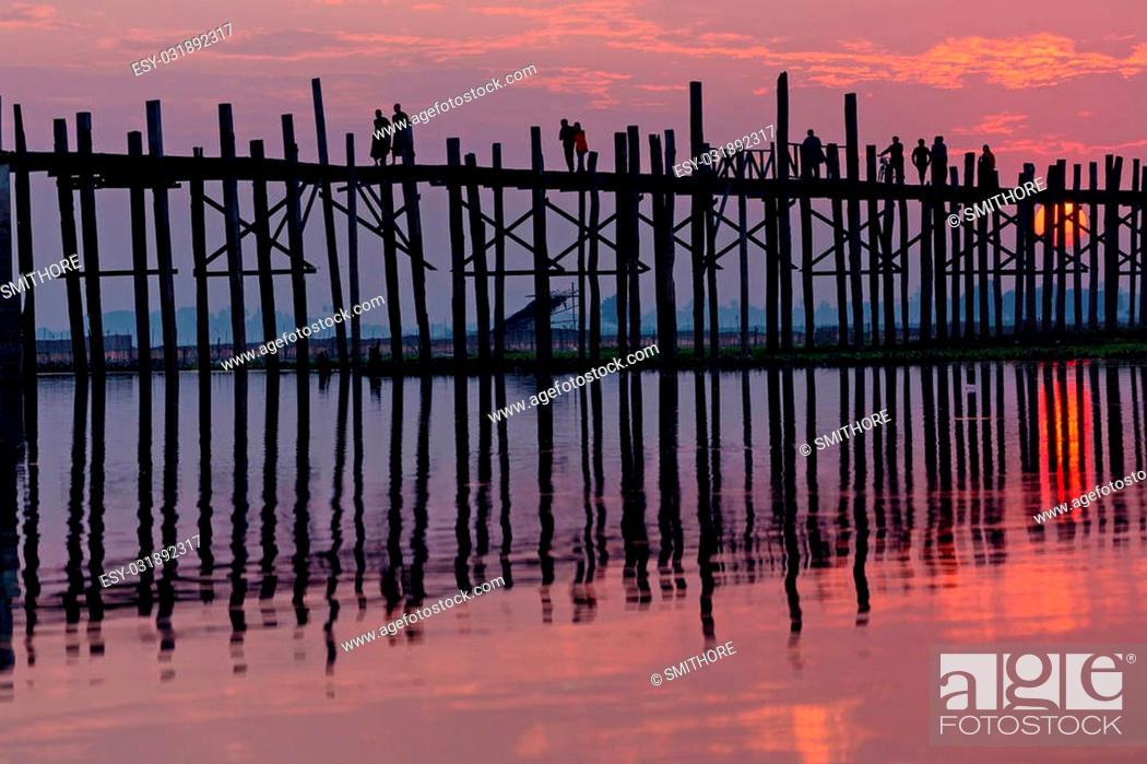 Stock Photo: U bein wooden teck bridge under red sunset in Myanmar.
