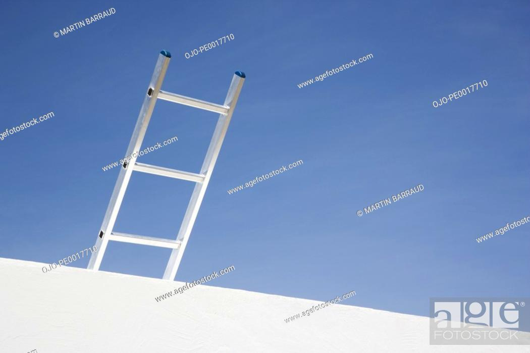 Stock Photo: Wall with ladder and blue sky.