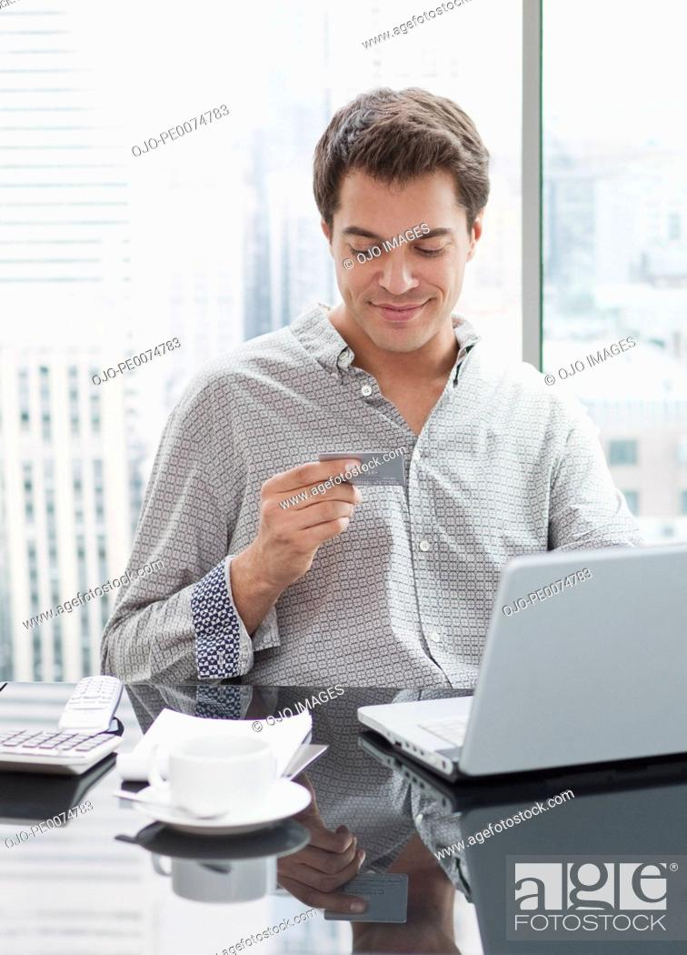 Stock Photo: Businessman using credit card to shop on internet.