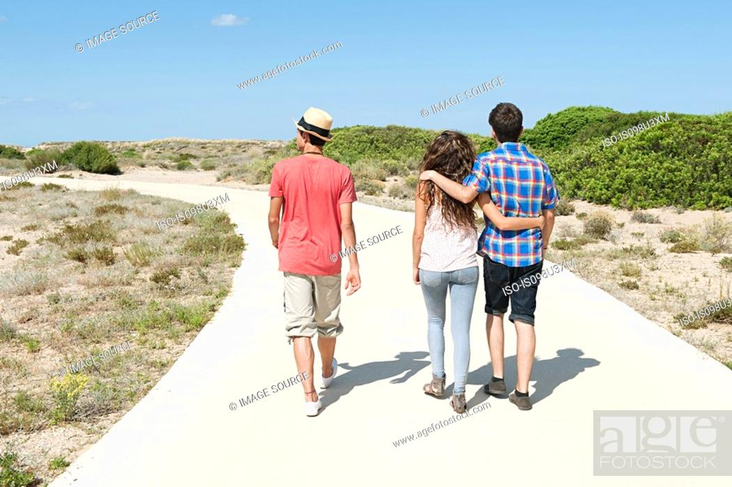 Stock Photo: Young friends walking down rural road, rear view.