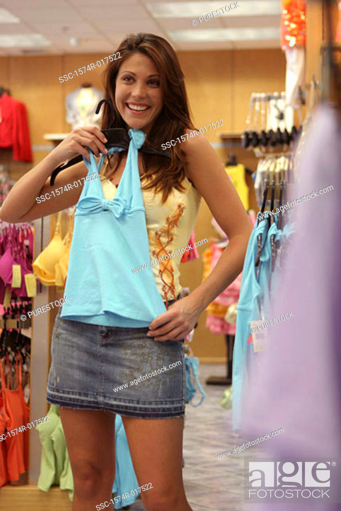 Stock Photo: Young woman holding a top in a clothing store.