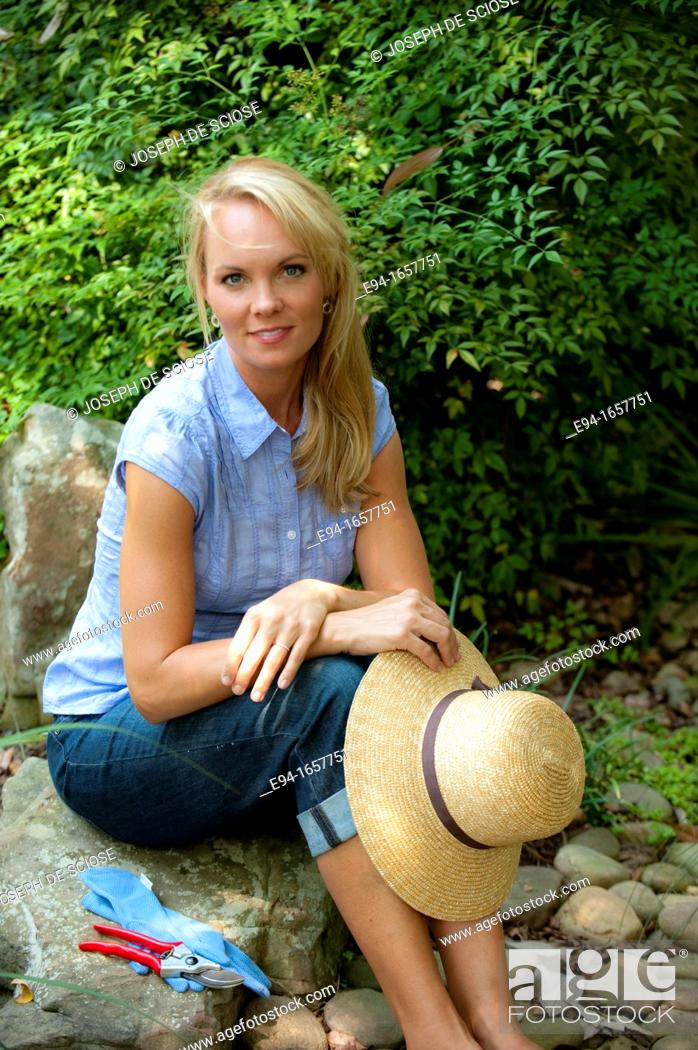 Stock Photo: Portrait of a 35 year old blond woman sitting on a rock holding a straw hat wearing a blue blouse and jeans in a garden setting looking at the camera.
