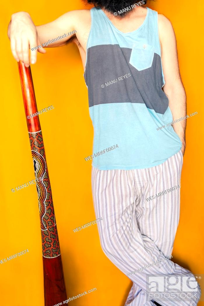 Imagen: Mature man with didgeridoo standing against yellow background.
