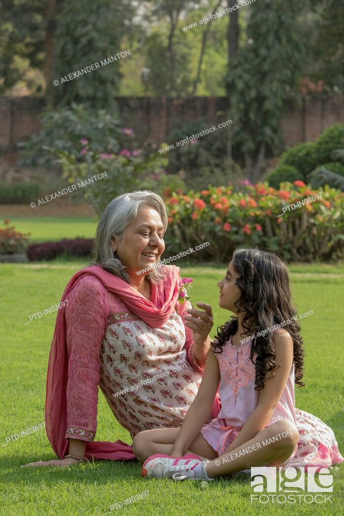 Stock Photo: Grandmother looking at flower with granddaughter (4-5) in garden.