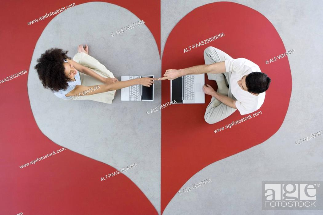 Stock Photo: Couple sitting face to face with laptop computers on heart shape, touching fingers, overhead view.
