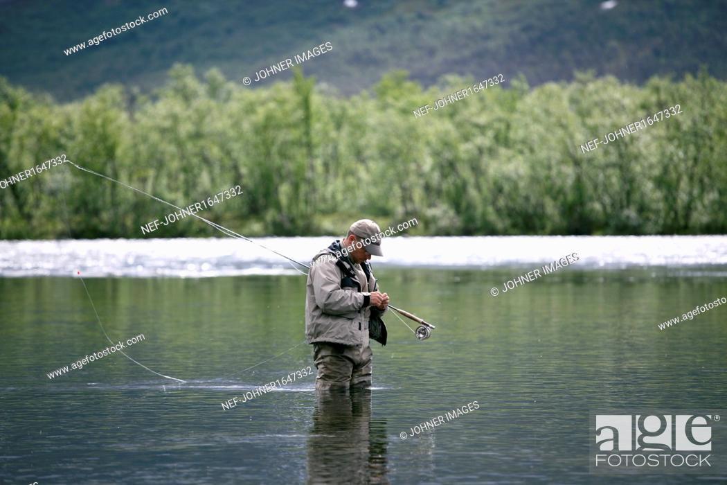 Stock Photo: Man fishing in mountain lake.