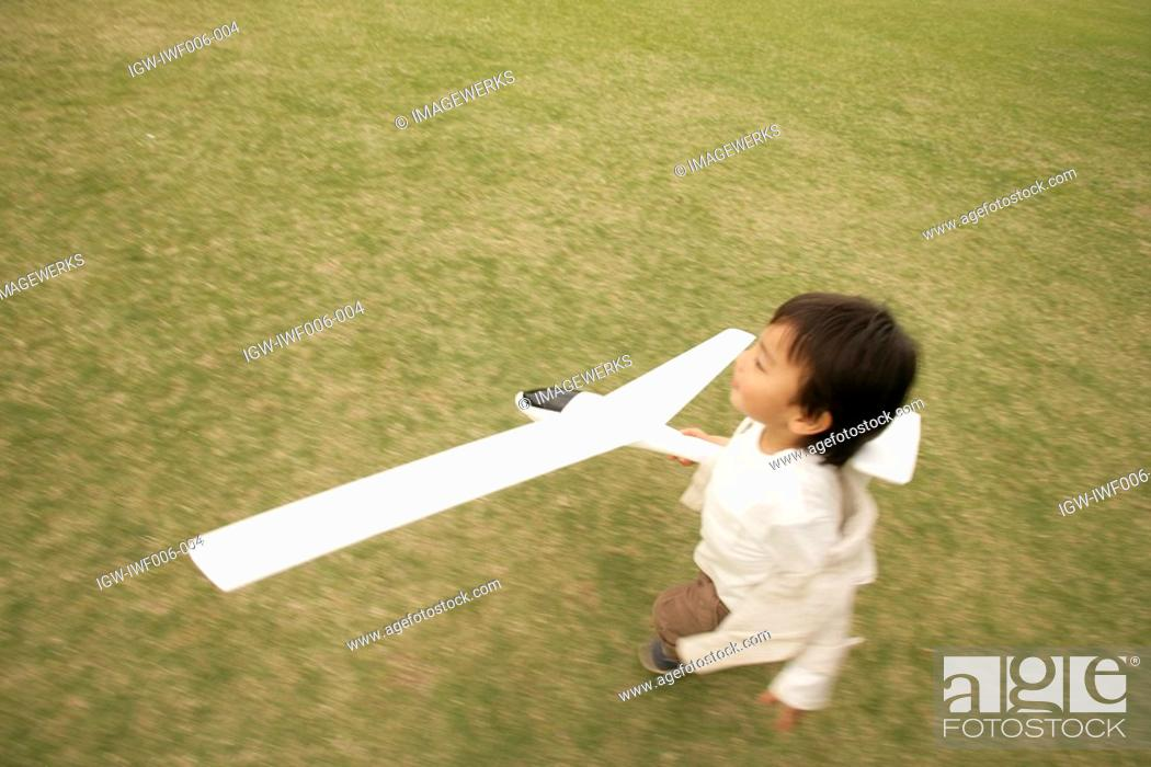 Stock Photo: A small boy running on the ground as he holds an aeroplane in his hand.
