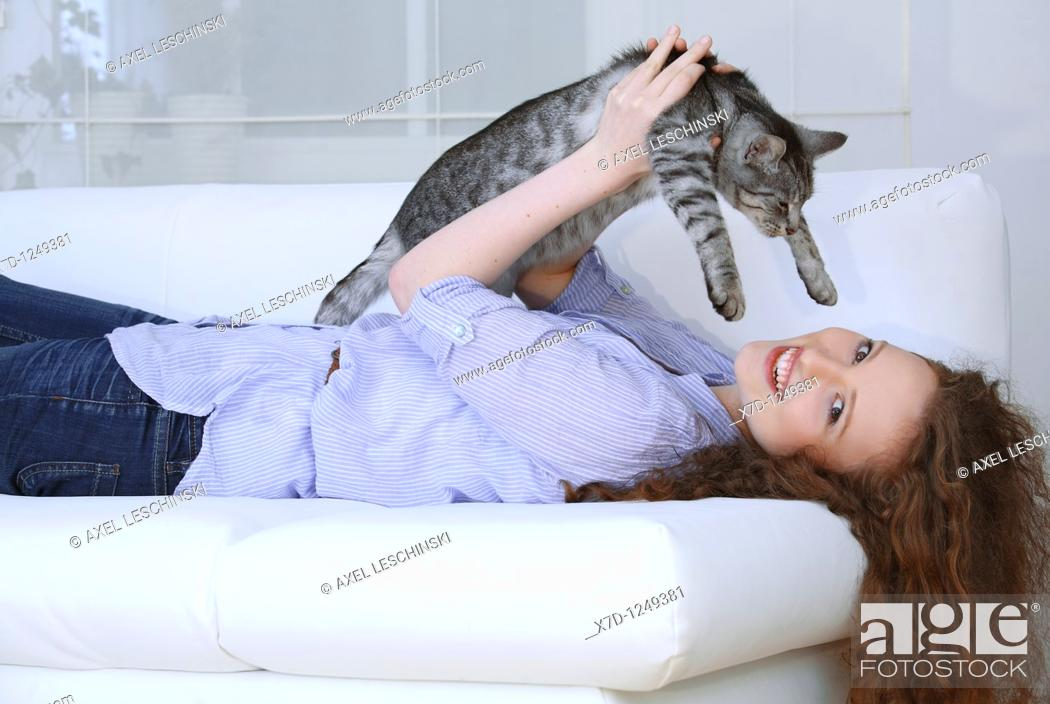 Stock Photo: young brunette woman fondling domestic cat.
