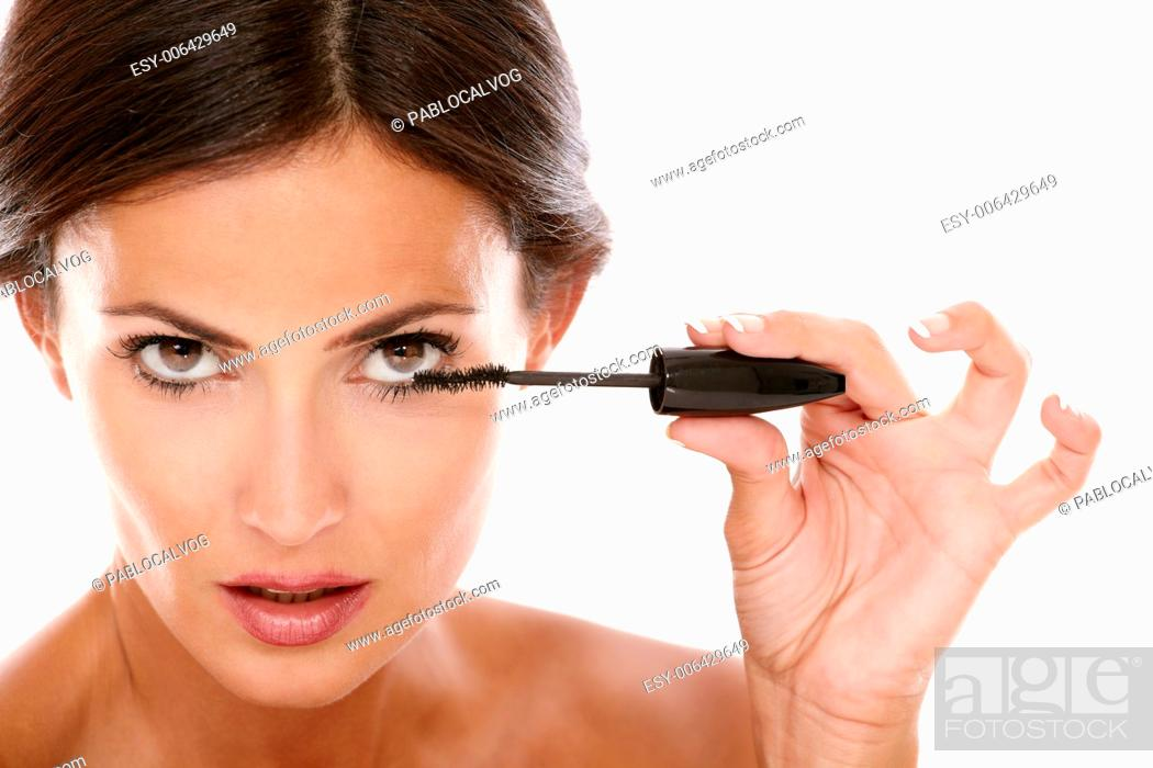 Stock Photo: Front view portrait of young latin woman using mascara to her eyelash with nude shoulders while looking at camera on isolated studio.