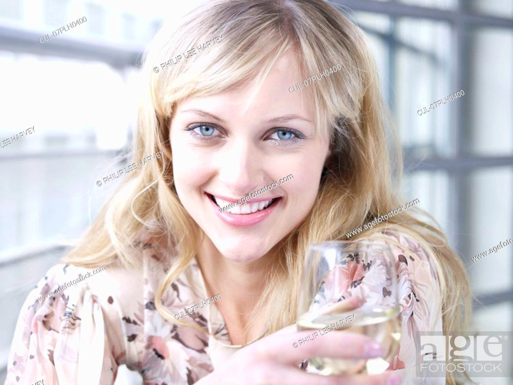 Stock Photo: Woman smiling to camera with wine glass.