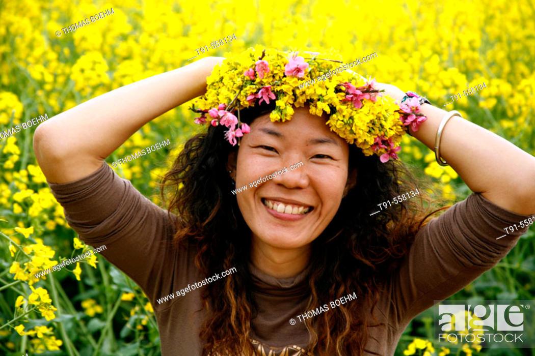 Stock Photo: Young beautiful chinese women wearing a rape flower crown. Luoping, Yunnan province. China.