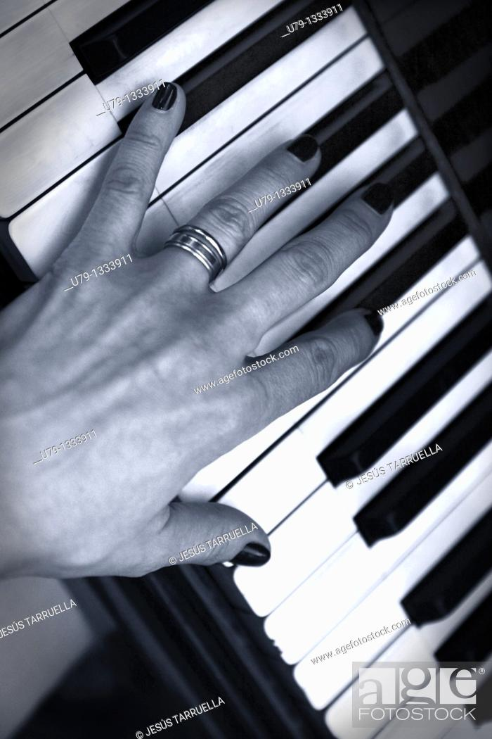 Stock Photo: Hand of a woman playing the piano.