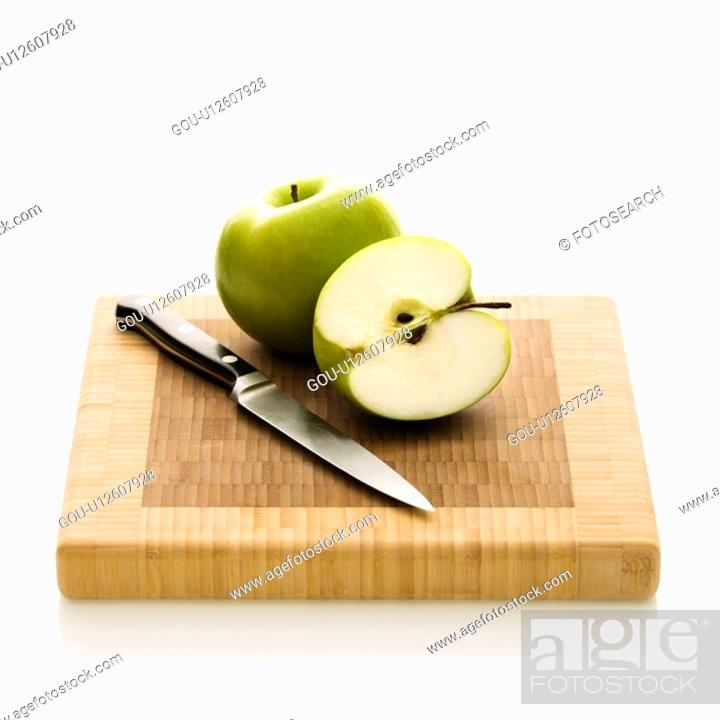 Stock Photo: Still life of green apples and knife on cutting board.