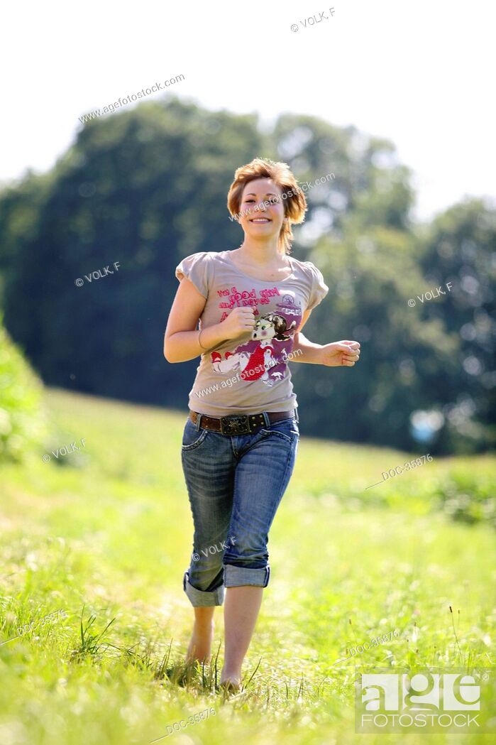 Imagen: Young woman runs laughing towards the camera - meadow in the background.