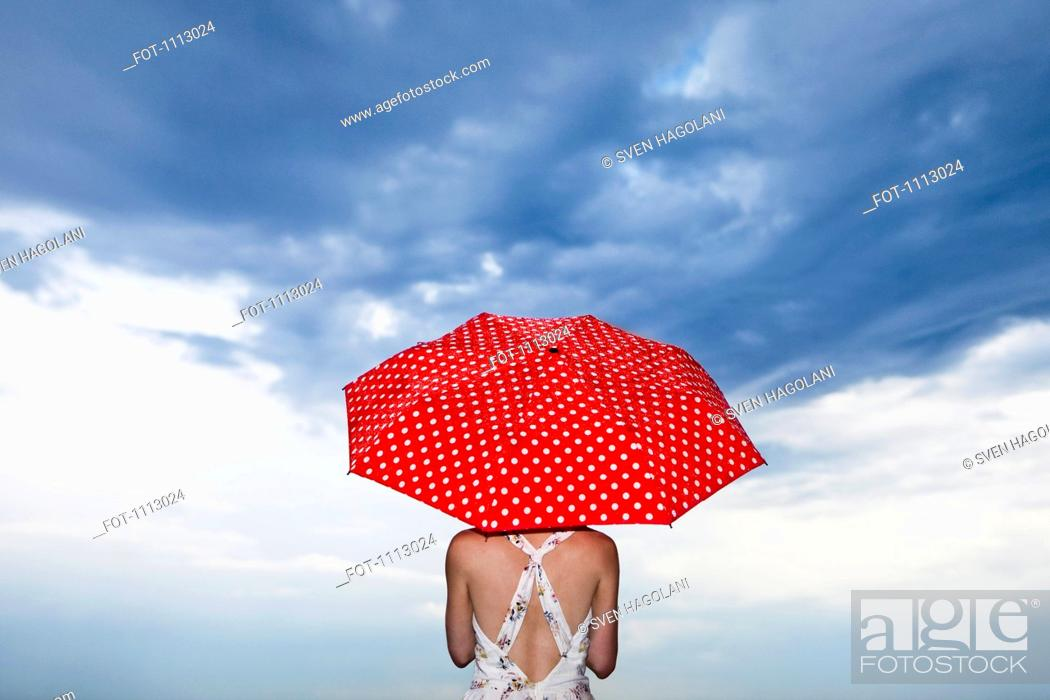 Stock Photo: A woman holding a red polka dot umbrella, rear view.