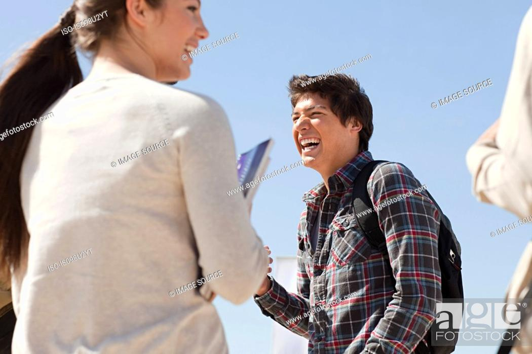 Stock Photo: High school students talking and laughing outside.