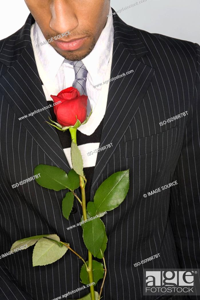 Stock Photo: Man holding a red rose.