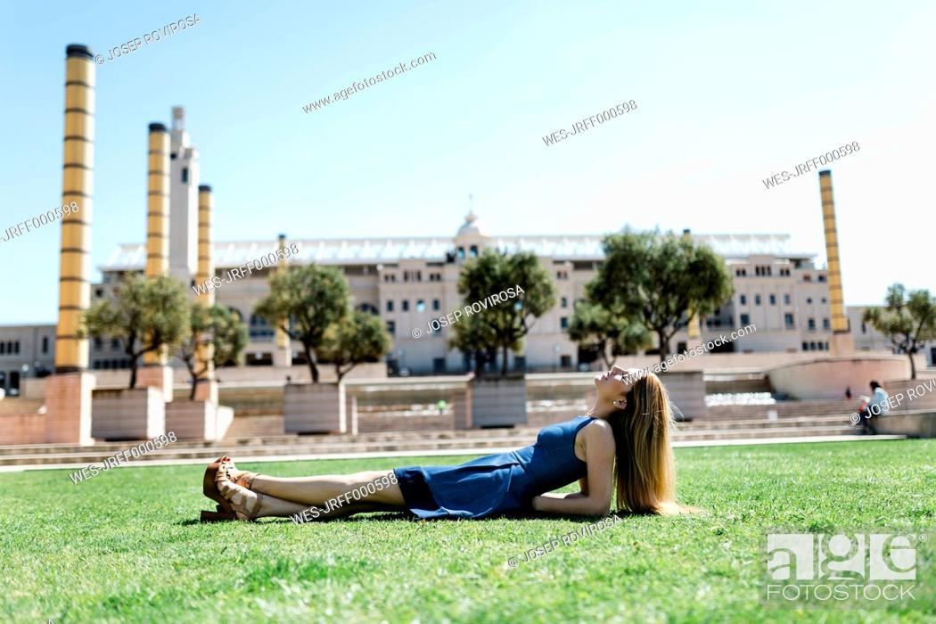 Stock Photo: Spain, Barcelona, woman relaxing on lawn in the city.