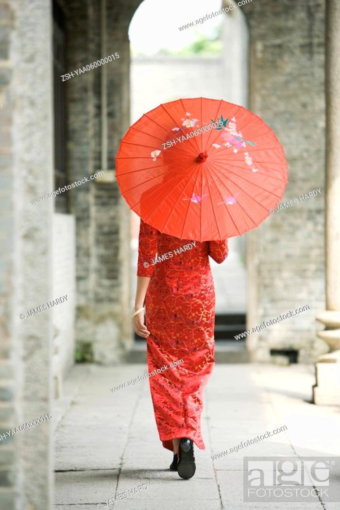 Stock Photo: Young woman dressed in traditional Chinese clothing walking with parasol, rear view.