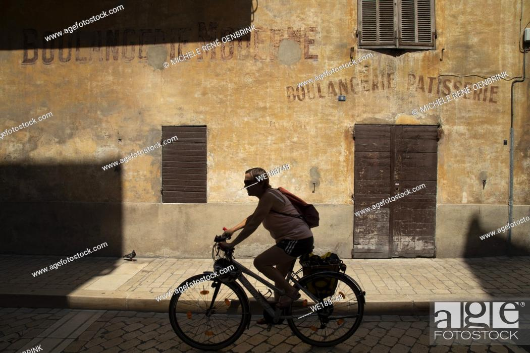 Stock Photo: Silhouette riding bicycle down street in french Mediterranean fishing port of Cassis, France, .