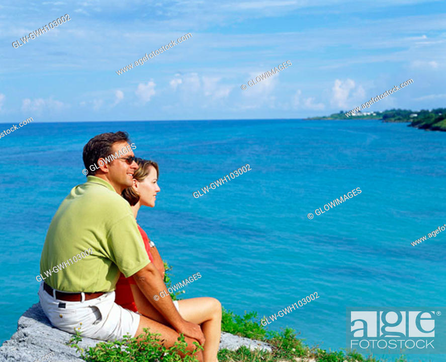 Stock Photo: Side profile of a young couple sitting together on a rock, Bermuda.