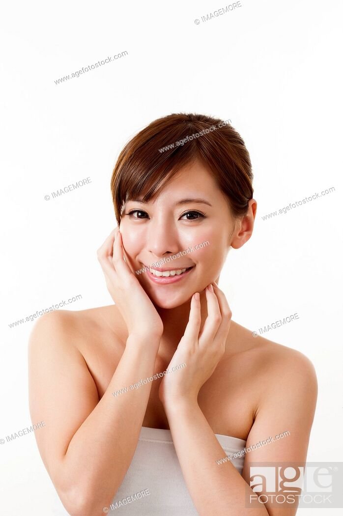 Imagen: Young woman smiling at the camera with hands on chin.