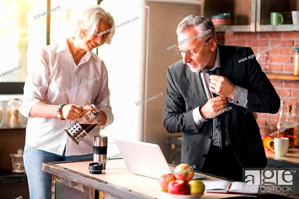 Stock Photo: Caring. Grey-haired businessman getting ready to his work while smiley lady taking care of him at the kitchen.