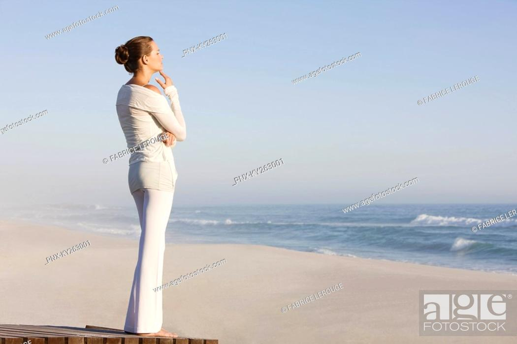 Stock Photo: Woman standing on a boardwalk looking at a view.