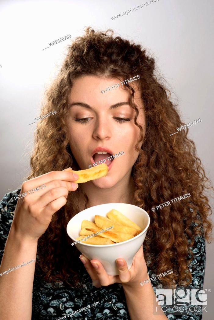 Stock Photo: Portrait of a Teenager Eating A Bowl Of Chips.