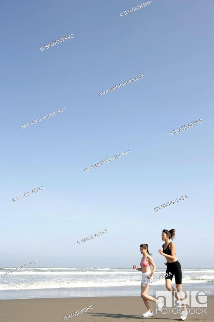 Stock Photo: Two women jogging on the seashore.