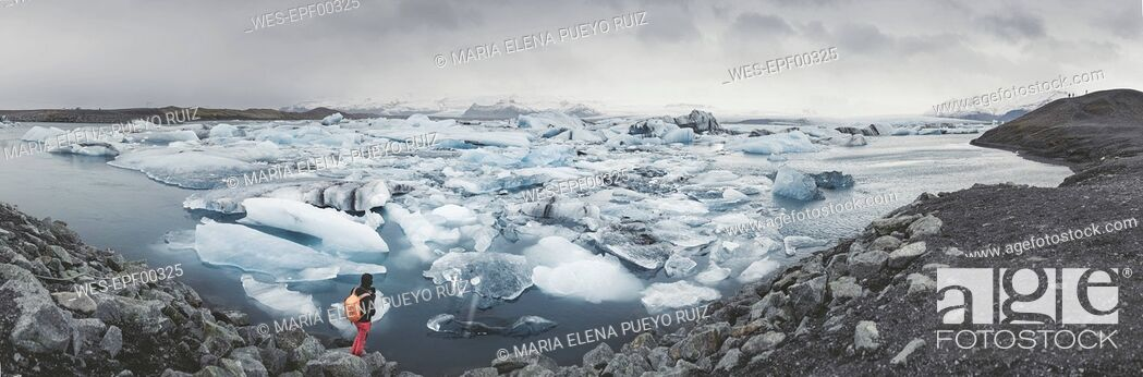 Stock Photo: Iceland, panoramic view of Joekulsarlon, glacial river lagoon with man standing in the foreground.